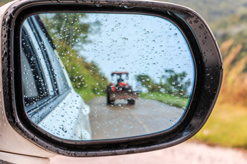 side rear-view mirror and raindrop on a car looking tractor