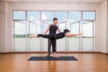 Yoga instructor correcting student performing Warrior 3 or Virabhadrasana 3 pose