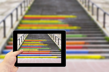 Tablet photography concept. Taking pictures on a tablet. Stairway in the form of pencils of rainbow colors