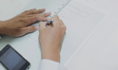 Close Up hands and smartphnoe of architect drawing