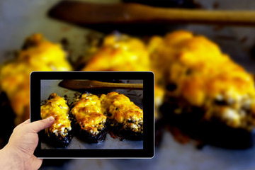 Tablet photography concept. Taking pictures on a tablet. Boats of eggplant zucchini stuffed with meat, rice, tomato and mushrooms with grated cheese on baking tray