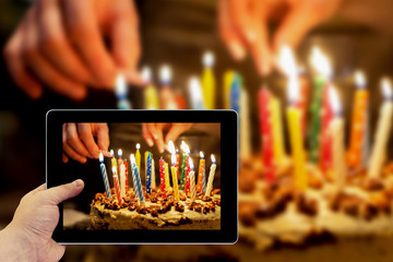 Tablet photography concept. Taking pictures on a tablet. Birthday cake with burning candles in the dark background