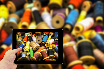 Tablet photography concept. Taking pictures on a tablet. Colored high contrasted threads for sewing
