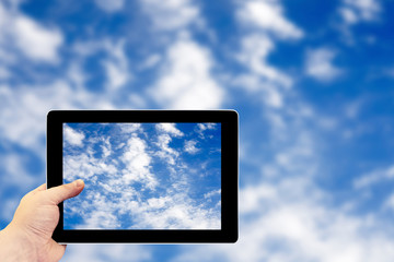 Tablet photography concept. Taking pictures on a tablet. Clouds on blue sky before the storm