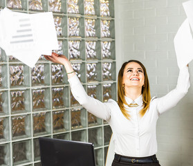 Business woman throws up her papers. lady manager smiling with happiness