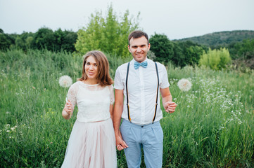 Happy Bride and groom walking on the green grass