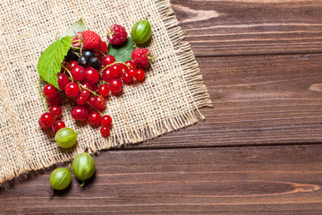 A mixture of ripe berries on a wooden table. Berries on a napkin, top view, empty space for text. Beautiful summer background