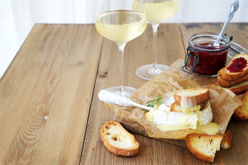 Baked camembert with toast and white wine in the background