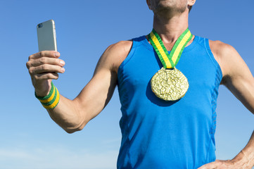 Brazilian gold medal athlete standing against blue sky using his mobile phone