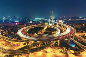 View over the Nanpu Bridge in Shanghai, China with car trails. Fantastic nighttime urban skyline.