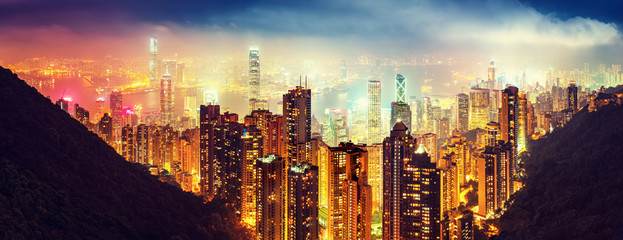 Panoramic view oover Victoria Harbor in Hong Kong, China, by night. Colorful travel background with illuminated skyscrapers seen from Victoria Peak.