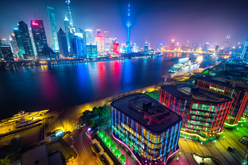Aerial panoramic view over a big modern city by night. Shanghai, China. Nighttime skyline with illuminated skyscrapers. Wall mural