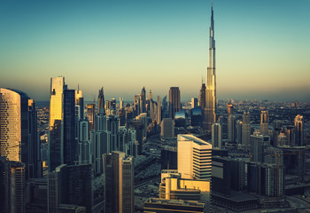 Downtown Dubai with many modern skyscrapers. Aerial view over the famous architecture of Dubai at sunset.