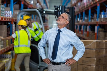 Focus of manager is looking shelves with hands on hips