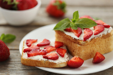 French toasts with cream cheese and strawberry on wooden table
