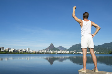 Athlete in white sport uniform standing with champion arms raised in front of Rio de Janeiro Brazil skyline at Lagoa Rodrigo de Freitas lagoon
