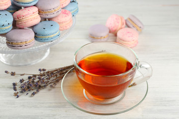 Tasty macaroons with tea on wooden table