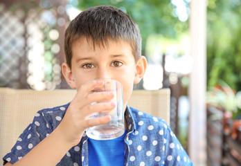 Cute boy drinking water in cafe