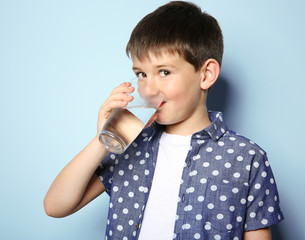 Cute boy drinking water on light background