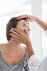 Cropped image of doctor checking woman eye