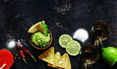 Tequila gold with sangrita chaser shots with lime slice with guacamole over old black metal surface, top view