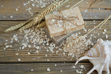 Natural handmade soap, oat flakes and wheat ears on wooden backg