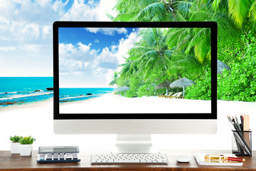 Conceptual image of a work space and computer desktop with coast and exotic trees in resort
