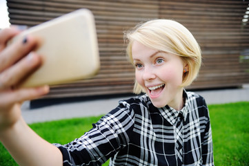 Young woman taking a self portrait with smart phone