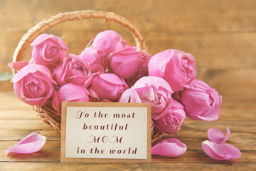 Happy Mothers Day. Fresh roses and greeting card on wooden background