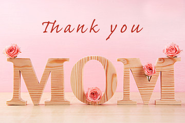 Happy Mothers Day. Holiday decoration with flowers and words on pink background
