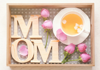 Happy Mothers Day. Mom word with cup of tea and flowers in box.