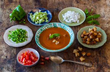 Gazpacho cold Spanish soup prepared the authentic way with garnishes served separately. Rustic retro vintage.