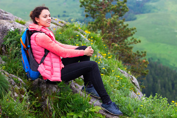 Woman Hiker with backpack relaxing on top of a mountain and look
