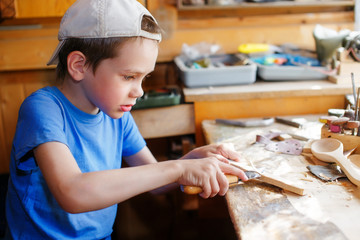 young carpenter working in a workshop. boy learning wood carving