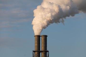 Weiß rauchender Industrie Schornstein vor blauem Himmel