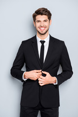 Cheerful happy man buttoning his black suit
