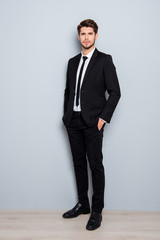 Full length portrait of handsome man in suit holding hands in po