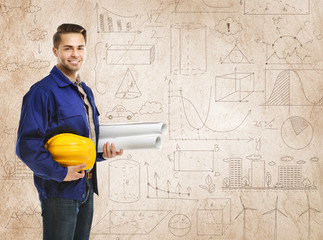 Engineer with blueprints and helmet on wall background