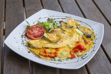 Omlette with herbs,vegetables and cheese in a plate on wooden table.