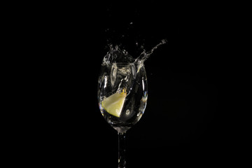Toss fruit into a glass of splash water and black background