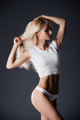 Fashion photo of beautiful blonde fit woman with magnificent hair posing on grey studio background