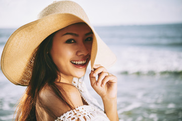 Portrait of pretty woman in straw hat on a beach