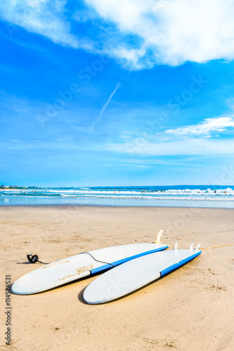 """Surfboards laying down on the sand at the beach."" zdjęć ..."