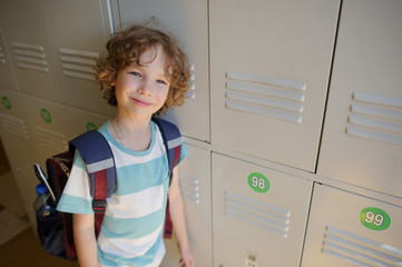 Little schoolboy standing near lockers in school hallway.