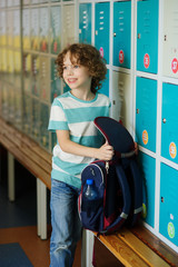 Little learner standing near lockers in school hallway