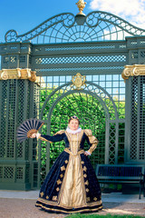 Historical cosplay. Beautiful woman in the similitude of Marguerite of Navarre, queen of France ancient dress in the garden near palace