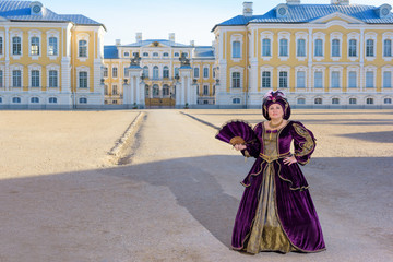 Historical cosplay. Beautiful woman in the similitude of Isabella d'Este Mantua, marquess of Italian ancient dress near palace