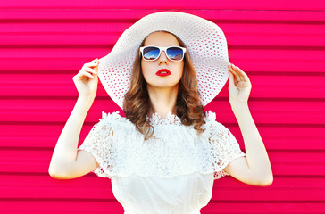 Fashion portrait pretty woman in white summer straw hat over col Wall mural