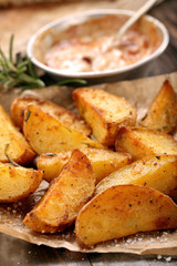 Roasted potatoes with dip on wooden table