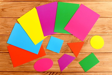 Colorful cardboard geometric shapes. Cut from cardboard triangle, square, oval, trapezoid, rectangle, circle. Children education concept. Sheets of colored paperboard on a wooden table